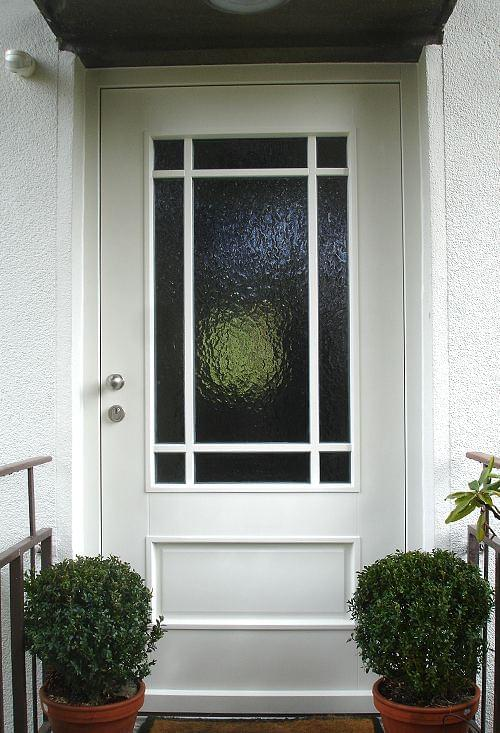 White wooden front door with glazing bars and structural glazing